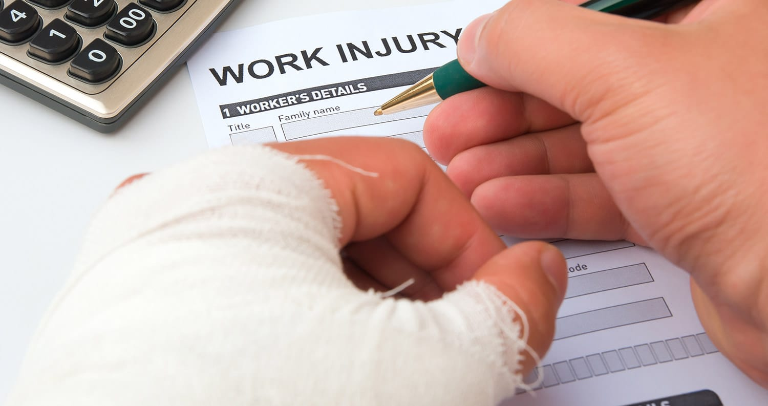 hands signing a workers compensation injury form one hand in a cast