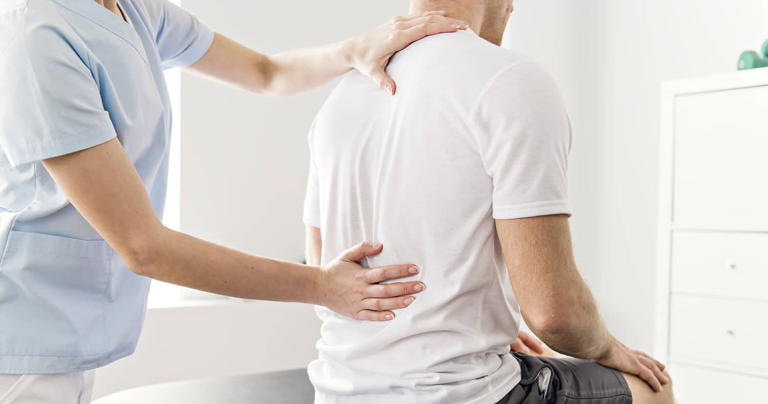 photo of a man with a back injury being examined by a medical professional