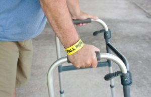 photo of an elderly man's hands on a walker with a fall risk wristband